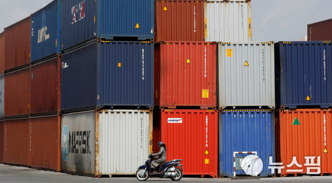 A woman rides a motorcycle as she passes containers at Hai Phong port, Vietnam September 25, 2018. Picture taken September 25, 2018. REUTERS/Kham